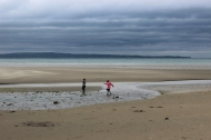 Children playing on the sandy beach in Enniscrone, County Sligo, Ireland on a rainy day