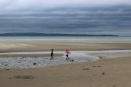 Children playing on the sandy beach in Enniscrone, County Sligo, Ireland on a rainy day